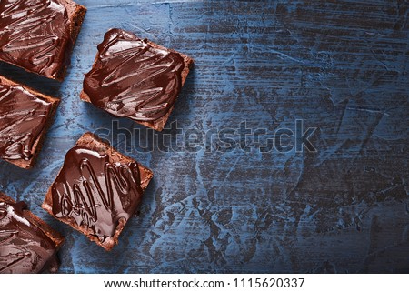 homemade chocolate brownies on dark blue background, top view, copy space