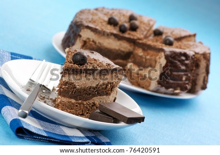 Homemade chocolate cake in white plates and checked napkin on cyan cloth. - stock photo