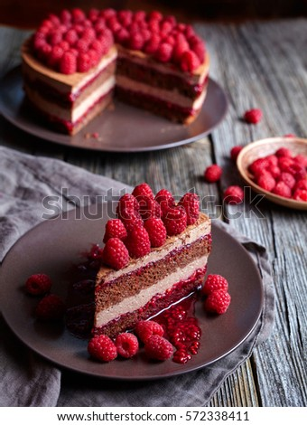 Homemade chocolate cake no bake cheesecake with biscuit and fresh raspberries on the rustic wooden table. Mousse chocolate. Concept of a romantic breakfast. Souffle dessert.