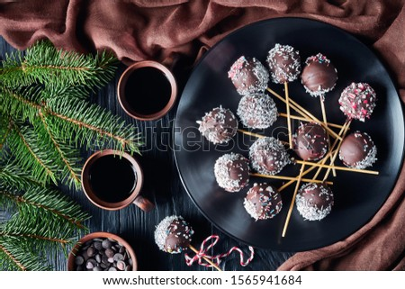 homemade chocolate cake pops sprinkled with crushed candies and coconut sprinkles on a black plate. cups coffee, fir limbs, brown cloth on a table, flatlay