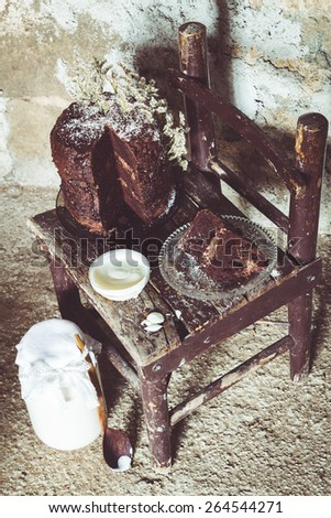 Homemade Chocolate Cake with Coconut Flakes and Dried Flower Decoration Next to a Bowl of Yogurt on a Small Vintage Chair. Glass Jar with a Wooden Spoon on the Floor. Rough Concrete Background