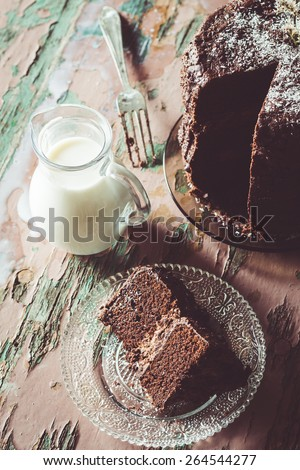 Homemade Chocolate Cake with Coconut Flakes and Dried Flower Decoration Next to a Glass Milk Jug on a Vintage Painted Wood Table. Moody Atmosphere