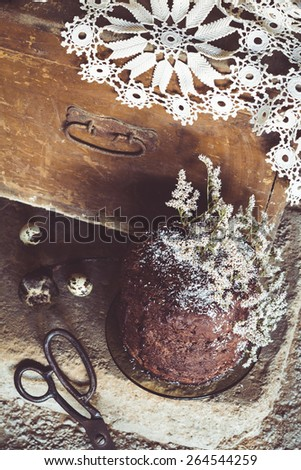 Homemade Chocolate Cake with Coconut Flakes and Dried Flower Decoration on a Rough Concrete Floor. Vintage Chest with a Lace Cover in the Background