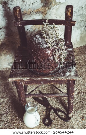 Homemade Chocolate Cake with Coconut Flakes and Dried Flower Decoration on a Small Vintage Chair. Glass Milk Jug and Iron Scissors on the Floor. Rough Concrete Background. Moody Atmosphere