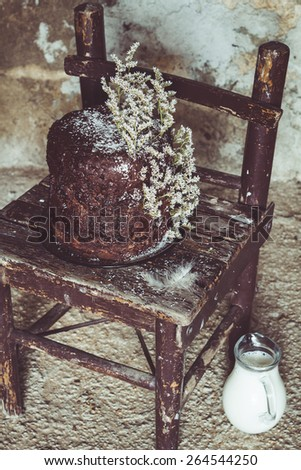 Homemade Chocolate Cake with Coconut Flakes and Dried Flower Decoration on a Small Vintage Chair. Glass Milk Jug on the Floor. Rough Concrete Background. Moody Atmosphere