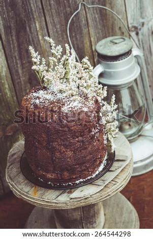 Homemade Chocolate Cake with Coconut Flakes and Dried Flower Decoration on a Small Vintage Wood Reel. Retro Lantern Included. Rusty Iron Floor and Moldy Wood Background