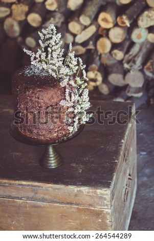 Homemade Chocolate Cake with Coconut Flakes and Dried Flower Decoration on a Vintage Chest. Cut Wood Background