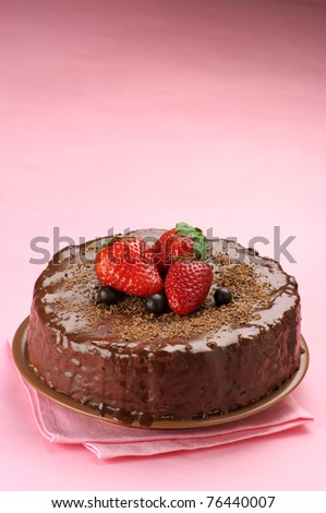 Homemade chocolate cake with strawberries on pink background.