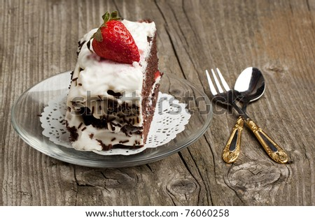 Homemade chocolate cake with whipped cream and fresh strawberry on old wooden table