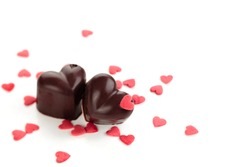 Homemade chocolate candies decorated with heart shaped sprinkles.