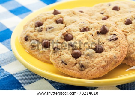Homemade, chocolate chip cookies, like Mom used to make, served on a yellow plate.  Shallow depth of field.