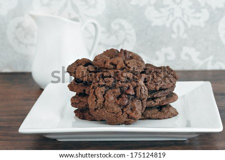 Homemade chocolate chocolate chip cookies stacked on a white plate.  Closeup front view.
