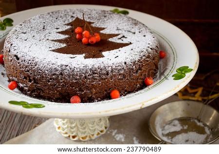 Homemade chocolate Christmas cake sprinkled with sugar powder