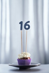 Homemade chocolate cupcake or muffin with number 16 sixteen on black plate with bright background. Birthday digital greeting card concept. High quality vertical photo