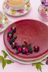 Homemade chocolate mousse cake with sweet cherry  jelly, decorated with sweet cherries, blackberries and flowers. On pink background.