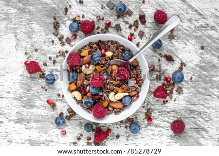 homemade chocolate muesli or granola in a bowl with a spoon, berries, dried fruits and nuts. healthy breakfast. top view