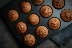 Homemade chocolate muffins in a baking dish on a dark background top view.