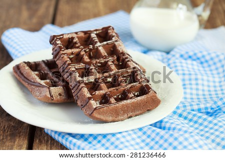 Homemade chocolate waffles with cocoa  from whole wheat flour, decorated with melted chocolate and powdered sugar on a white plate and a pitcher of milk on a wooden table, selective focus