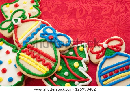 Homemade Christmas cookies in the shape of Christmas trees and holiday ornaments which forms a nice border.  Red silk background with poinsettias in the fabric.