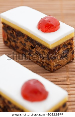 Homemade Christmas fruit cake with a red cherry. Shallow DOF - stock photo