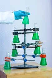 homemade Christmas tree from flasks with green liquids. the hand of a chemist or medic in a glove holds a flask.