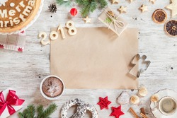 Homemade Christmass cookies, number year 2018, desserts, gift, cinamon, berries, dried orange, hazelnuts, cup of coffee, red christmas tree toys on a beige wooden background.