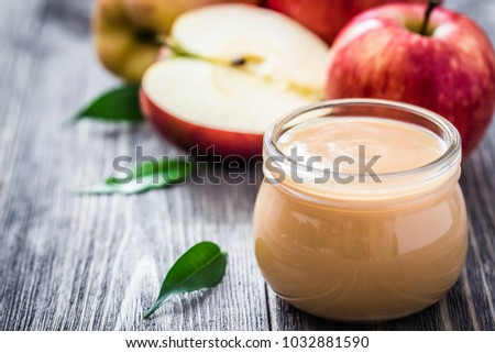 Homemade cinnamon canned applesauce in glass jar and red ripe apples on rustic wooden background. Selective focus, space for text. stock photo