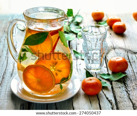 Homemade citrus infused water in a jug on a rustic background in a sunny day