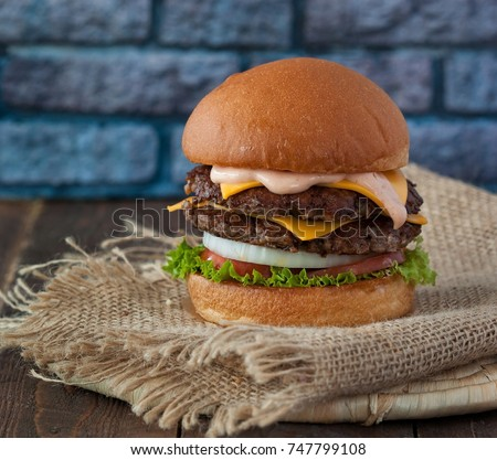 Homemade classic beef burger with double patty, cheese, lettuce, onion, tomato and sauce on the rustic linen table cloth. Delicious food Stock photo ©