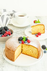 Homemade classic vanilla sponge cake or biscuit sprinkled with powdered sugar and fresh berries on top on a white plate on a light wooden background