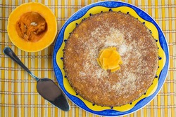 Homemade coconut and pumpkin cake on a yellow tablecloth