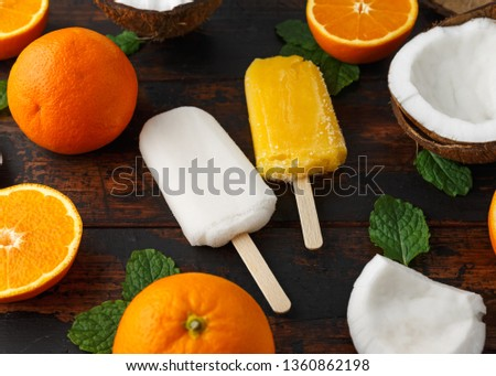 Homemade Coconut, Orange popsicles, ice lolly, on wooden table. Summer food