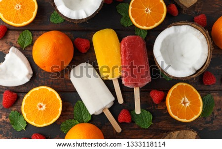 Homemade Coconut, Orange, raspberry popsicles, ice lolly, on wooden table. Summer food.