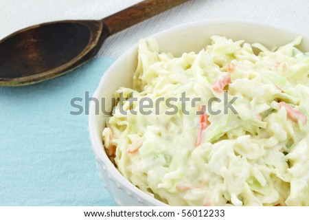 Homemade coleslaw in a white bowl with an old wooden spoon in the background.