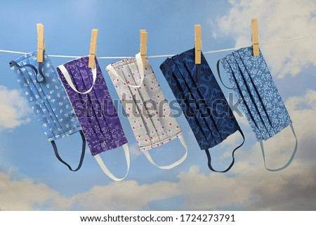 Photo of  Homemade community face masks from cloth as protection against coronavirus pandemic are hanging on a clothesline, blue sky with clouds