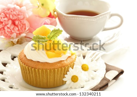 homemade confectionery, mango cupcake with english tea on background for gourmet dessert image