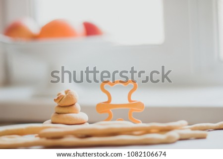 Homemade cookies in the form of ringlets and a shape for cutting a teddy bear on the background of a light window in the defocus. In the defocus is a vase in the fruit. Side view. #1082106674