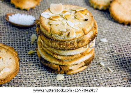 Homemade Cookies. Tasty homemade shortbread biscuits with almonds and coconut flakes close-up on a dark background. Gluten-free sugar-free pastries, healthy desserts concept