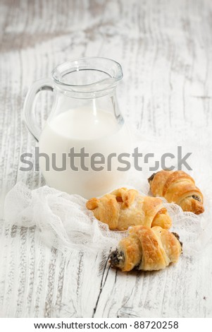 Homemade cookies with jug of milk on white wooden table