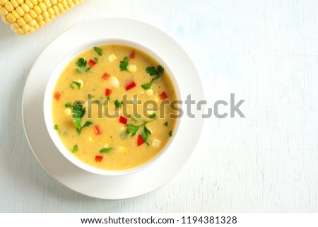 Homemade Corn Chowder Soup in white bowl. Vegetarian creamy corn soup with greens and vegetables.