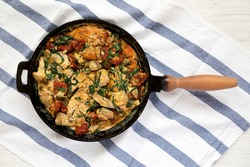 Homemade Creamy Tuscan Chicken in a cast-iron pan, overhead view. Flat lay, top view, from above.
