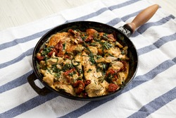 Homemade Creamy Tuscan Chicken in a cast-iron pan, side view.