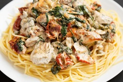 Homemade Creamy Tuscan Chicken with Pasta on a white plate on a black background, side view. Close-up.