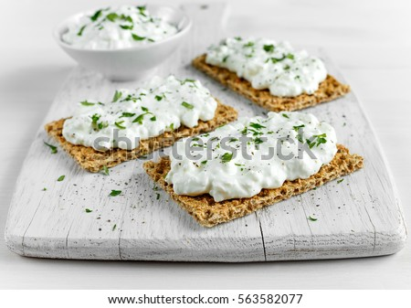 Homemade Crispbread toast with Cottage Cheese and parsley on white wooden board.