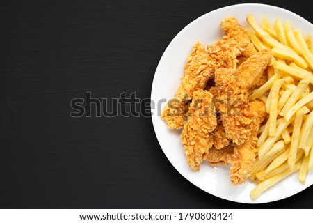 Homemade Crispy Chicken Tenders and French Fries on a white plate on a black background, top view. Copy space. Stock photo ©