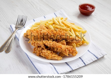 Homemade Crispy Chicken Tenders and French Fries on a white plate, side view. Stock photo ©