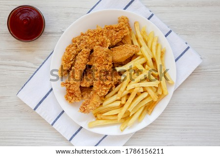 Homemade Crispy Chicken Tenders and French Fries on a white wooden background, top view. Flat  lay, overhead, from above.