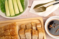 Homemade Crispy Pork Belly or Deep Fried Pork in whole and cut pieces, made by using Air Fryer, serving on wooden tray with special spicy dark sauce and fresh vegetables