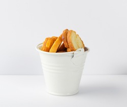 Homemade crunchy croutons with garlic, herbs and spices in white bucket isolated. Round spicy bruschetta crackers, seasoning rusks or small fried bread snacks