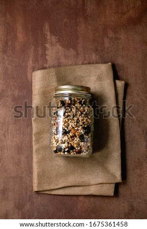 Homemade crunchy puffed millet grain granola with dried fruits and nuts in glass maison jar on textile napkin over brown texture background. Flat lay, space. Healthy food eco friendly breakfast Photo stock ©